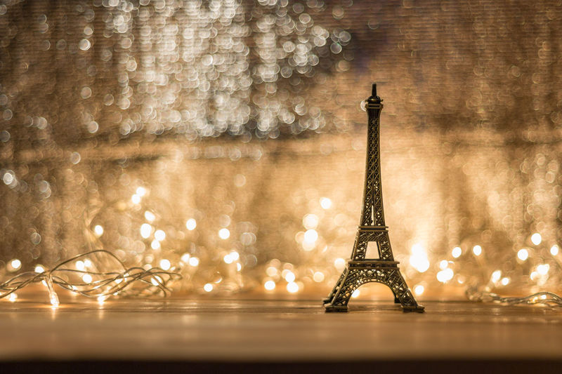 Close-up of small replica eiffel tower with illuminated string lights on table
