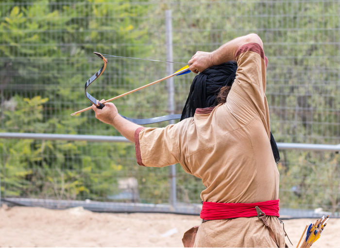 """Jerusalem, Israel, September 30, 2018 : The participants of the festival in traditional costume of the Saracen warrior show the art of archery at the annual festival """"Jerusalem Knights"""" Business Fun International Jerusalem Israel Jerusalem Knights Saracen Show Warrior Advertisement Art Battle Design Exhibition Festival Fighter Friendship Game Magician Medieval Samurai Spectator Symbol Traditional Costume Triumph Watching"""