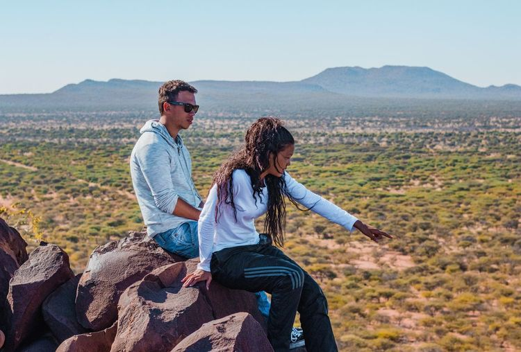 Young couple sitting on mountain against sky