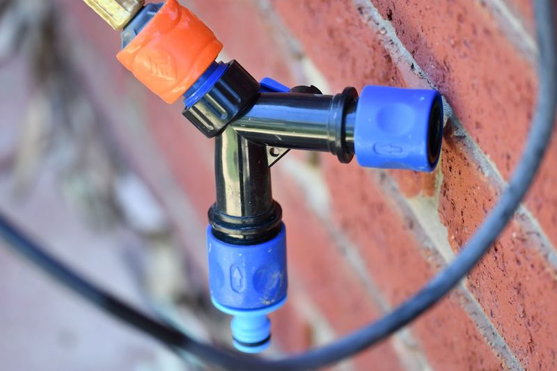 Hose Connectors Orange Color EyeEm Selects Close-up Day No People High Angle View Blue Outdoors Connection Wall - Building Feature Faucet Garden Hose Focus On Foreground Selective Focus