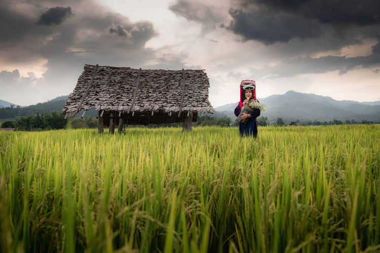 Woman standing at farm against cloudy sky