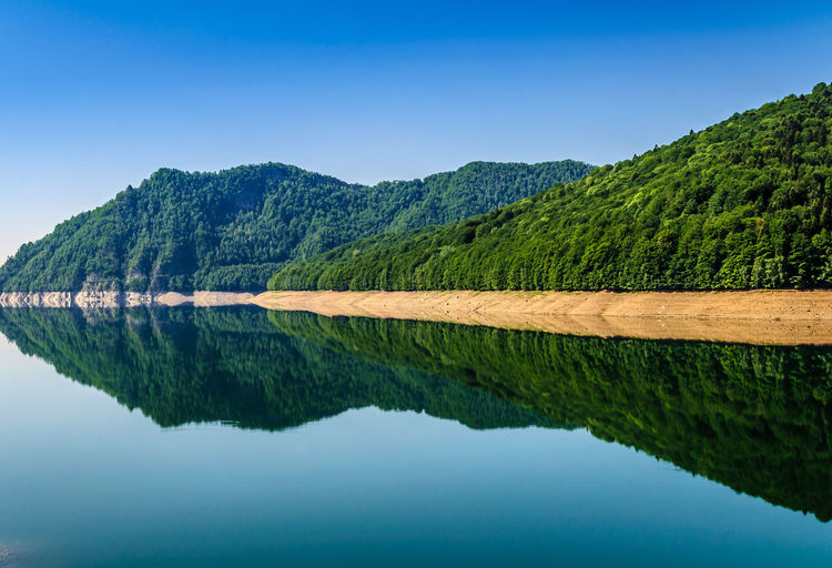Scenic View Of Mountains Reflecting In Lake Against Clear Sky
