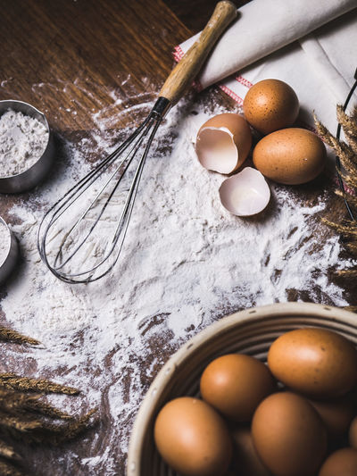 High angle view of eggs with flour on table