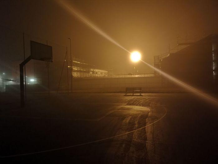 Illuminated street lights on road against sky at night