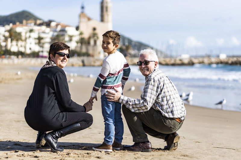 Portrait of happy grandparents with grandson crouching at beach