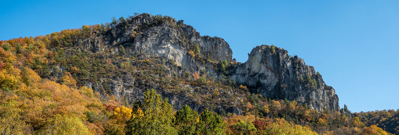 Low angle view of rocks against sky during autumn