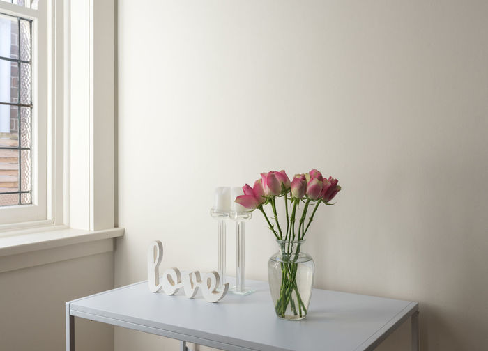 Flowers In Vase With Text On Table At Home