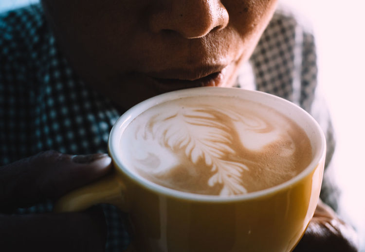 Close-up of woman drinking coffee from cup at cafe
