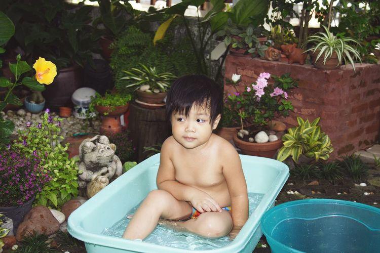 Shirtless boy sitting in bathtub at yard