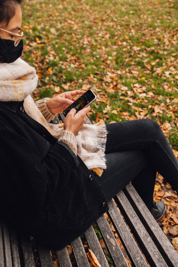 Man using mobile phone while sitting on bench