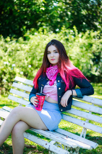 Beautiful young woman having drink while sitting on bench at park