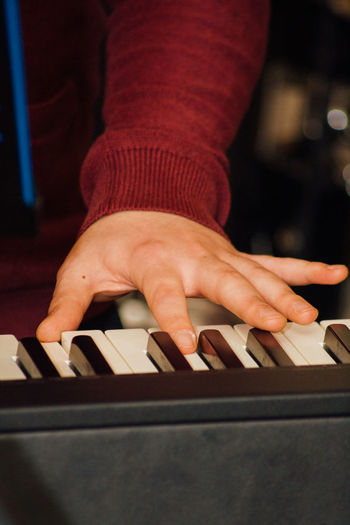 Midsection of person playing piano in studio