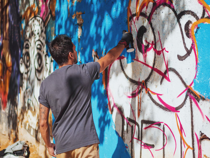 Rear view of young man spraying graffiti on wall
