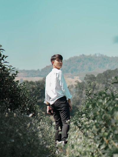 Portrait of man walking by plants against clear sky