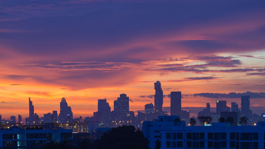 Scenic view of illuminated city at sunset