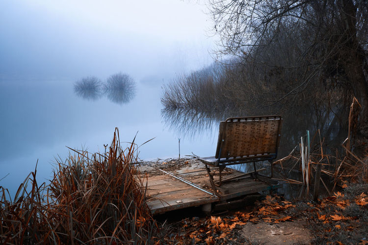 Abandoned chair by lake against sky