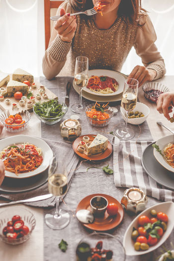 Midsection of woman eating food at table