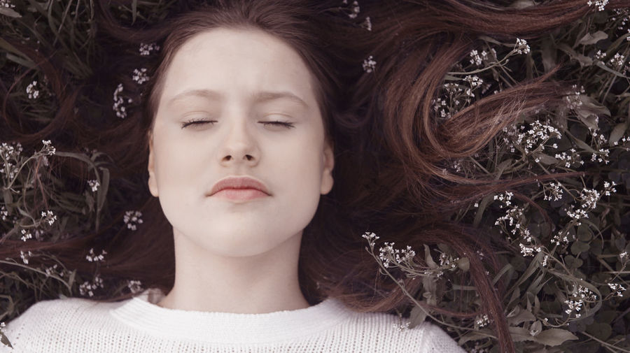 Adult Beautiful Woman Brown Hair Close-up Contemplation Eyes Closed  Front View Hair Hairstyle Headshot Human Face Innocence Leisure Activity Lifestyles Long Hair Lying Down One Person Portrait Real People Women Young Adult