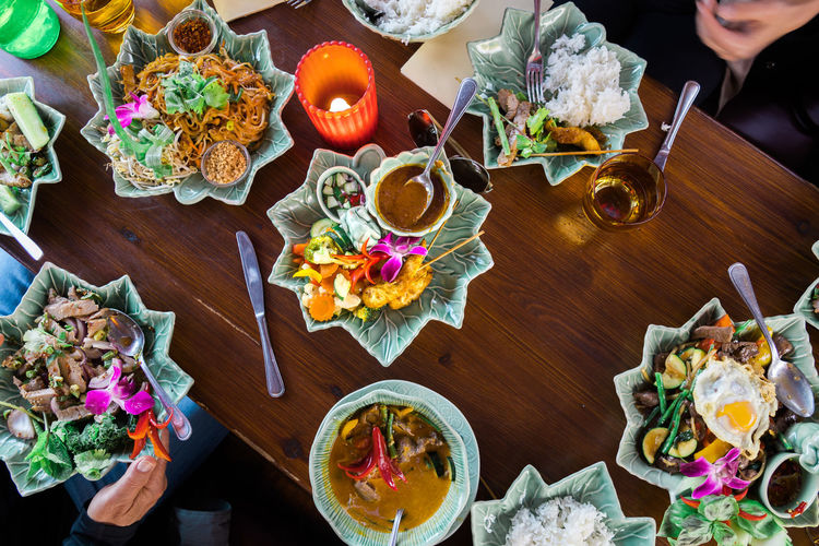 High angle view of table full of thai food Ready To Eat Thai Foods Thailand Bouquet Candle Dessert Directly Above Flower Flower Arrangement Flowering Plant Food Food And Drink Freshness Hand High Angle View Human Body Part Human Hand Indoors  Nature Plant Ready-to-eat Real People Table Thai Food