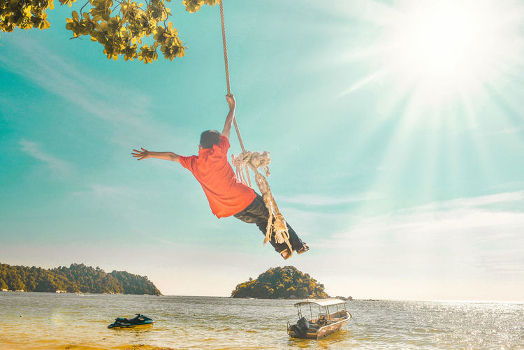 Low angle view of boy swinging on rope swing at beach against sky