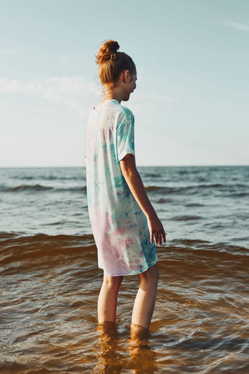 Girl standing in a water spending a free time on a beach over a sea at sunset during summer vacation