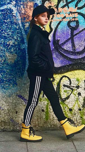 Side view of man wearing hat standing against graffiti wall