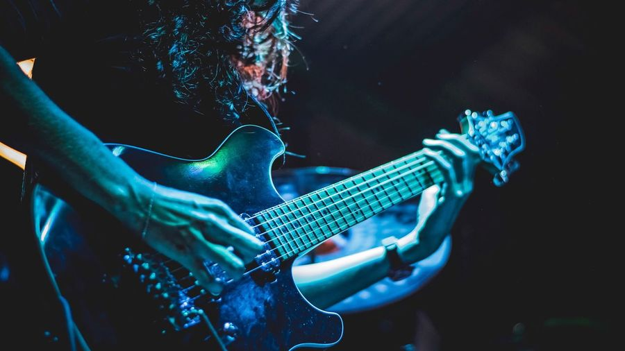 Music Musical Instrument Guitar String Instrument Arts Culture And Entertainment Performance Musician One Person Playing Plucking An Instrument Midsection Rock Music Guitarist Night Musical Equipment Artist Stage Skill  Stage - Performance Space Enjoyment
