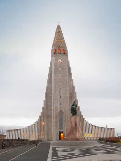 Hallgrímskirkja is a Lutheran (Church of Iceland) parish church in Reykjavík, Iceland. At 73 metres (244 ft), it is the largest church in Iceland and among the tallest structures in Iceland. The church is named after the Icelandic poet and clergyman Hallgrímur Pétursson (1614 to 1674), author of the Passion Hymns.Situated in the centre of Reykjavík, it is one of the city's best-known landmarks and is visible throughout the city. State Architect Guðjón Samúelsson's design of the church was commissioned in 1937. He is said to have designed it to resemble the basalt lava flows of Iceland's landscape. The design is similar in style to the expressionist architecture of Grundtvig's Church of Copenhagen, Denmark, completed in 1940. Leif Eriksson Reykjavik Architecture Astronomy City Cityscape Clock Clock Tower Day Hallgrìmskirkja Hallgrímur Pétursson History Iceland Memories No People Outdoors Place Of Worship Sky Sunset Tourism Tourist Attraction  Tower Travel Travel Destinations Vivid International