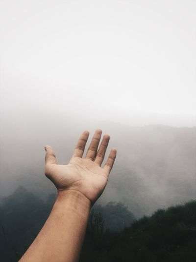 Cropped hand of man gesturing against mountains during foggy weather
