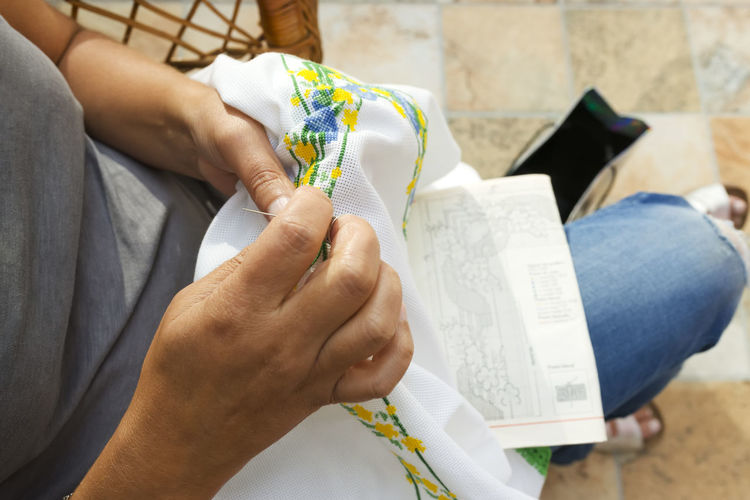 Low Section Of Woman Embroidering On Fabric