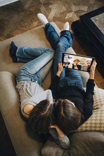 High angle view of friends relaxing on floor at home