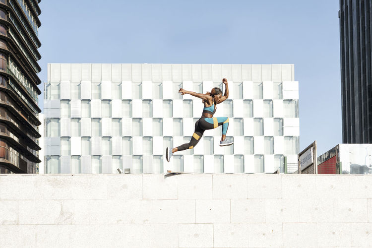 Full length of young woman jumping against building