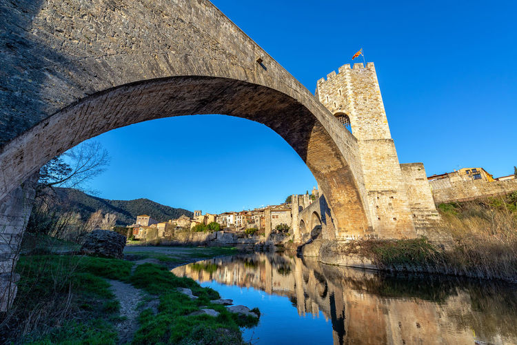Low angle view of arch bridge over river against clear blue sky