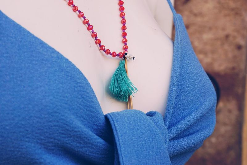 Midsection of woman wearing bead necklace
