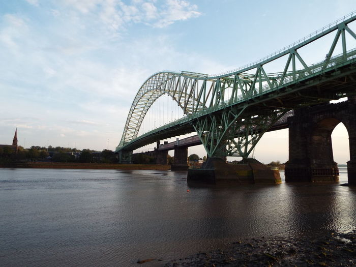 Low angle view of silver jubilee bridge over river against sky on sunny day