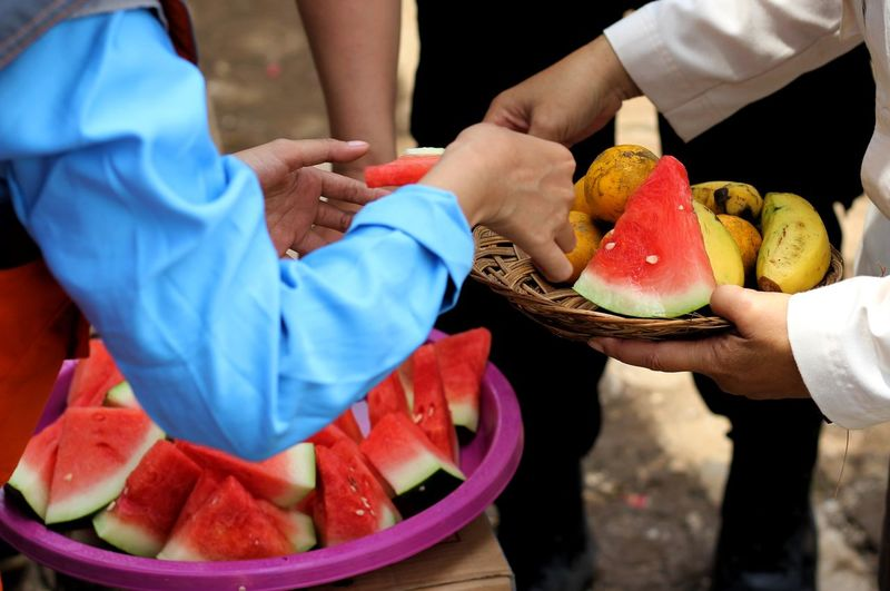 share fruits Watermelon Banana Orange Women Men Low Section Occupation Holding Volunteer Charity And Relief Work Donation Box Social Services Non-profit Organization Community Outreach