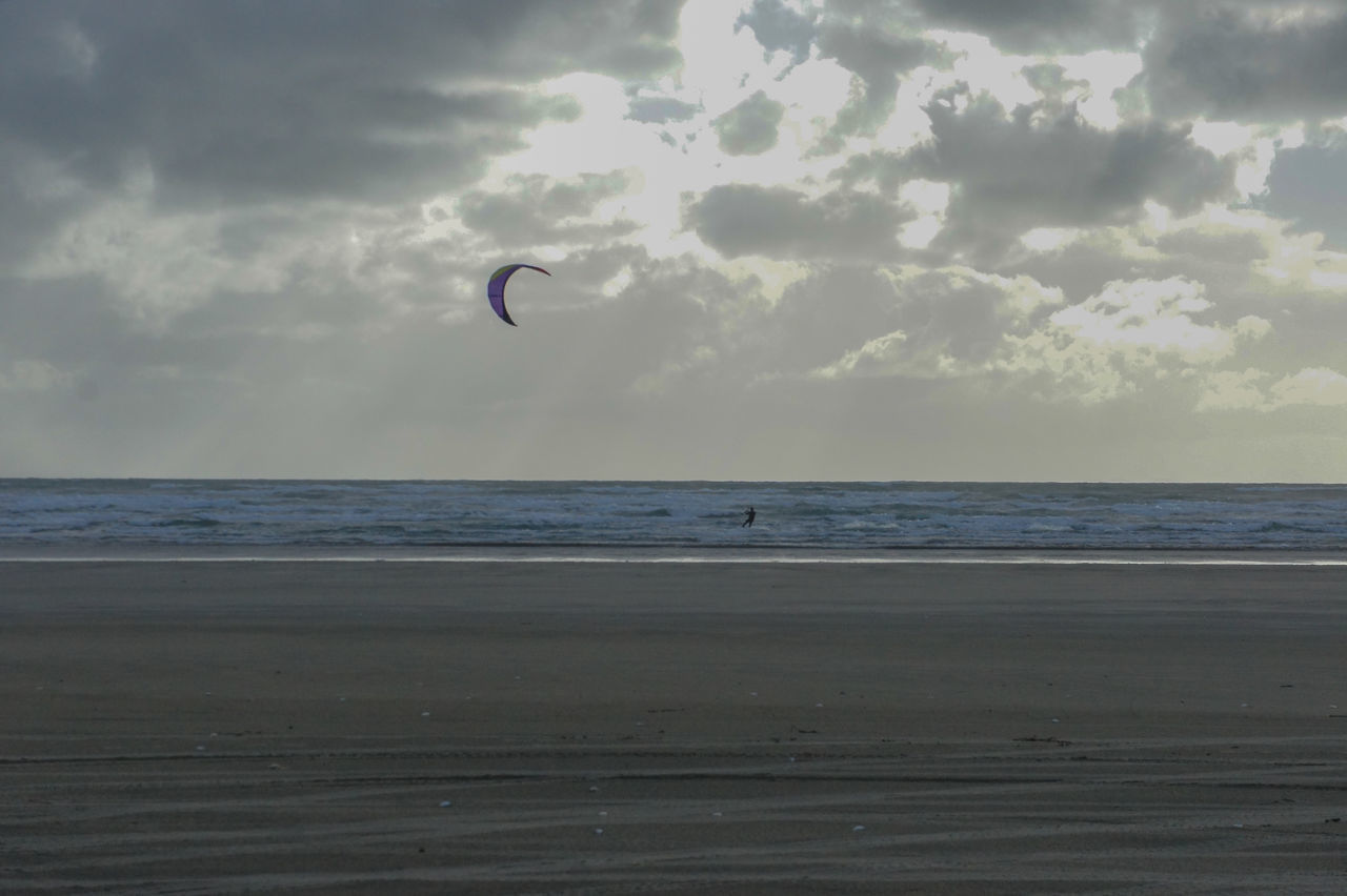 sea, sky, horizon over water, horizon, water, land, beauty in nature, cloud - sky, extreme sports, scenics - nature, adventure, beach, sport, parachute, paragliding, nature, tranquil scene, kiteboarding, unrecognizable person, outdoors