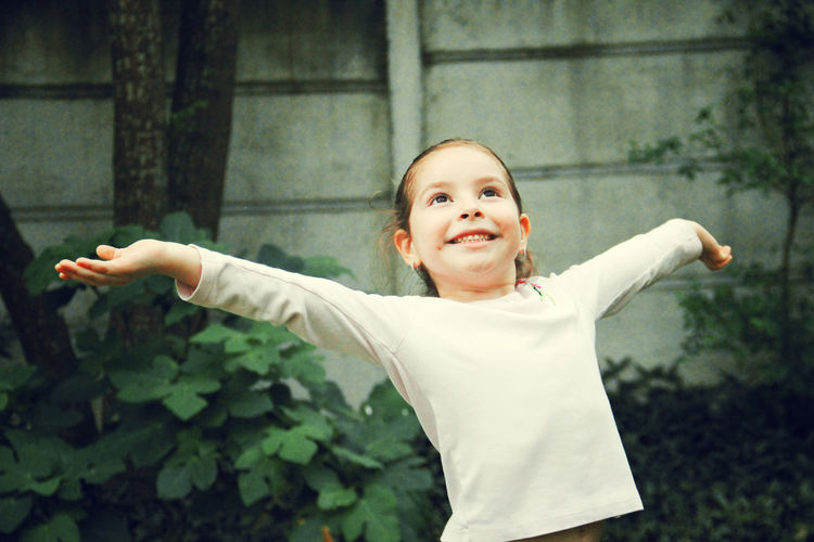 Cute girl with arms outstretched standing against plants