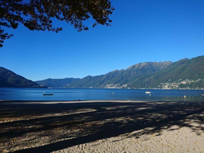 View of calm blue sea against mountain range
