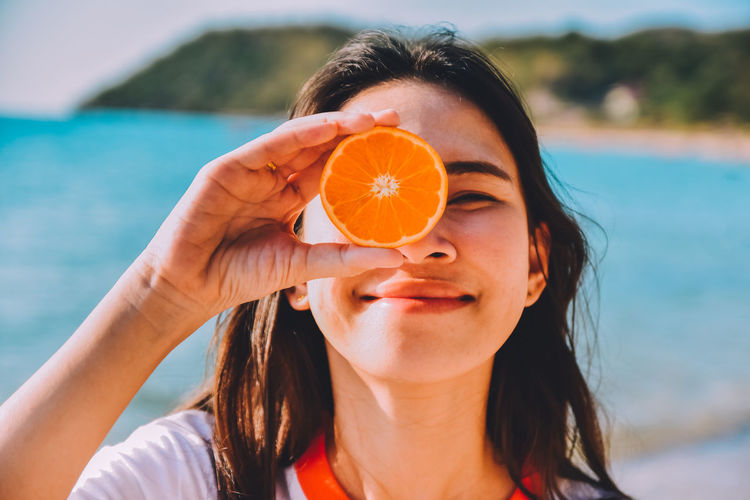 Close-up of smiling woman holding orange fruit at beach
