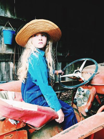 Girl wearing straw hat while sitting on tractor in barn
