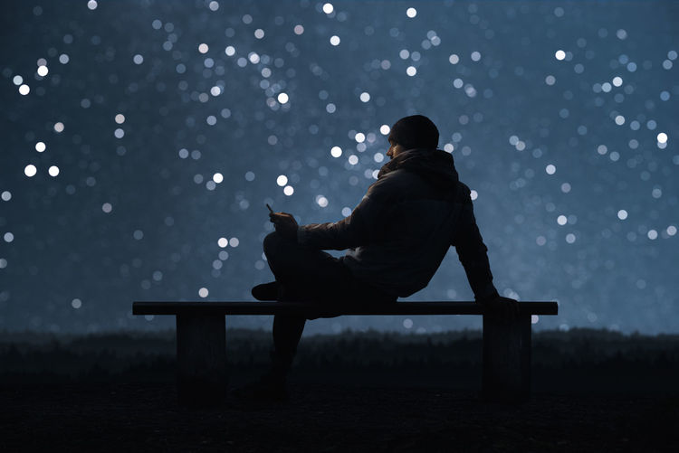 Man using phone while sitting on seat against star field