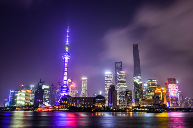 Illuminated oriental pearl tower in city by river huangpu at night