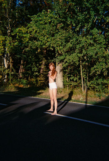 Portrait of woman standing on road against trees