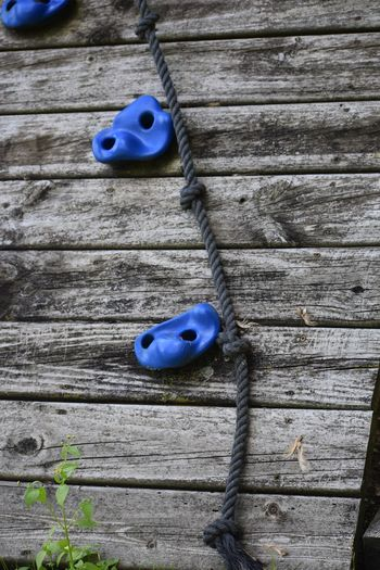 Rock climbing wall Swingset Playground Rock Climbing Plastic Blue Black Rope Climb Blue Wood - Material No People Close-up Day Textured  Pattern Still Life Plank Wood