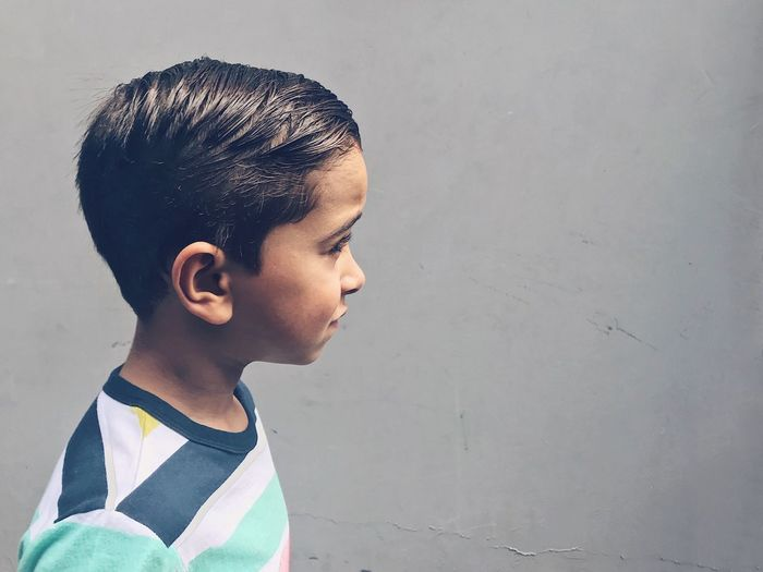 Portrait of cute boy standing against wall