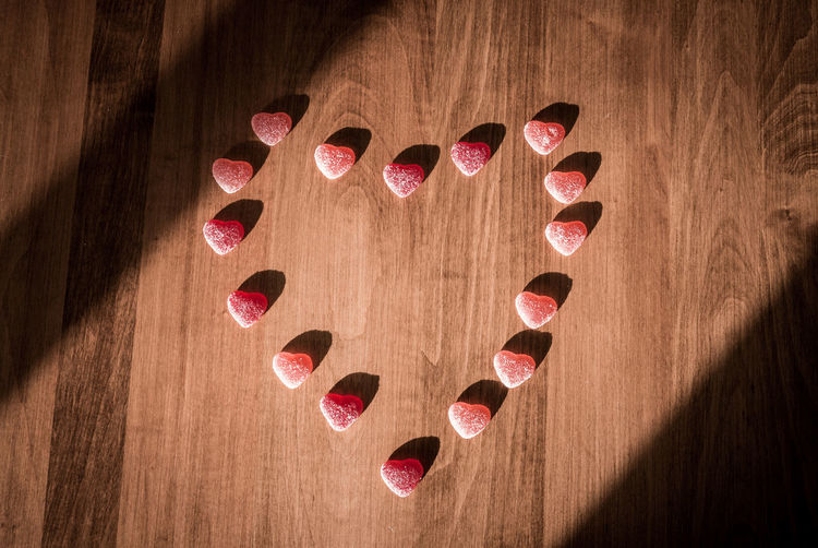 Directly above shot of candies arranged in heart shape on hardwood floor