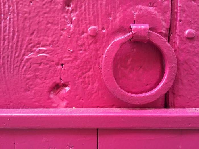 Close-up of pink metallic ring knocker on door