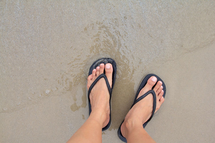 Low section of bare feet on sand