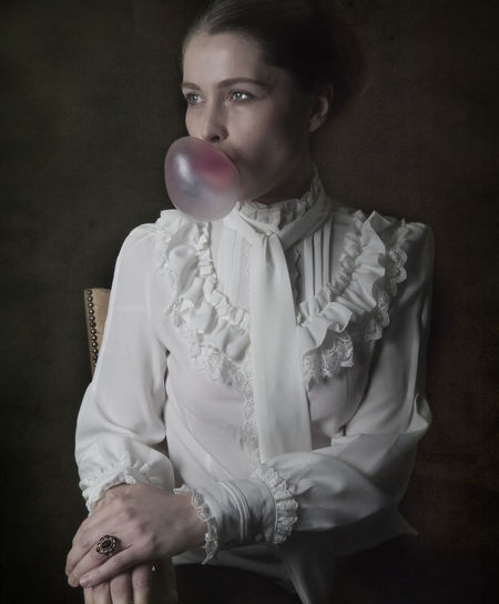 Woman blowing bubble gum while siting on chair against black background
